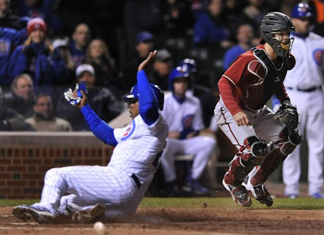 Arizona Diamondbacks catcher Tuffy Gosewisch right, waits for the throw while Chicago Cubs' Luis Valbuena left, slides safely into home plate on a Nate Schierholtz sacrifice fly during the fifth inning of a baseball game in Chicago, Tuesday, April 22, 2014. (AP Photo/Paul Beaty)
