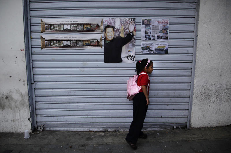 A girl stands by a closed storage area where a poster hangs of Venezuela's President Hugo Chavez in Caracas, Venezuela, Friday, April 20, 2012.  Chavez is in Cuba to continue with cancer treatment. (AP Photo/Ariana Cubillos)
