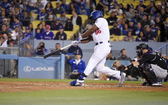 Los Angeles Dodgers' Yasiel Puig hits a solo home run as Colorado Rockies catcher Chris Iannetta watches during the sixth inning of a baseball game Tuesday, May 22, 2018, in Los Angeles. (AP Photo/Mark J. Terrill)