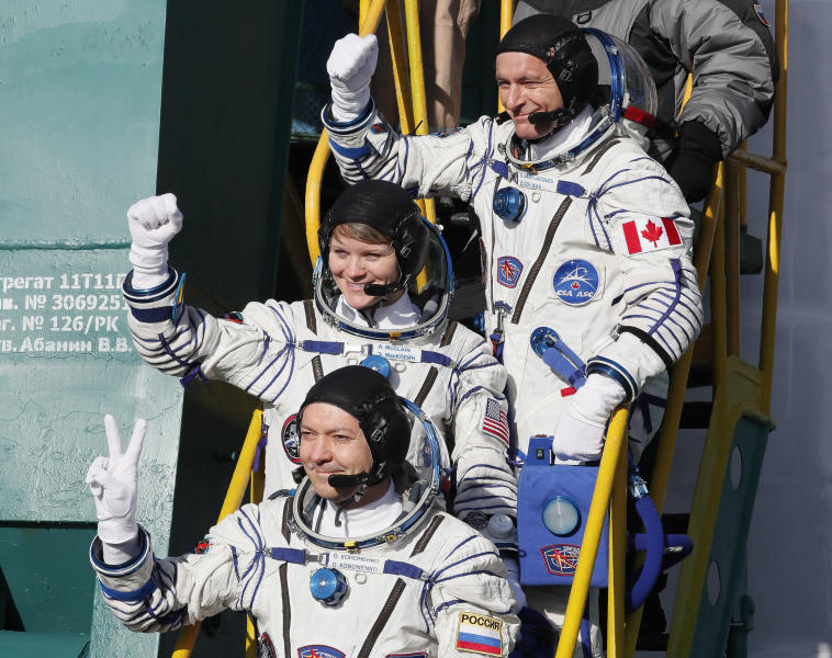U.S. astronaut Anne McClain, centre, Russian cosmonaut Оleg Kononenko and CSA astronaut David Saint Jacques, top, crew members of the mission to the International Space Station, ISS, wave as they board to the rocket prior to the launch of Soyuz-FG rocket at the Russian leased Baikonur cosmodrome, Kazakhstan, Monday, Dec. 3, 2018. (AP Photo/Shamil Zhumatov, Pool)