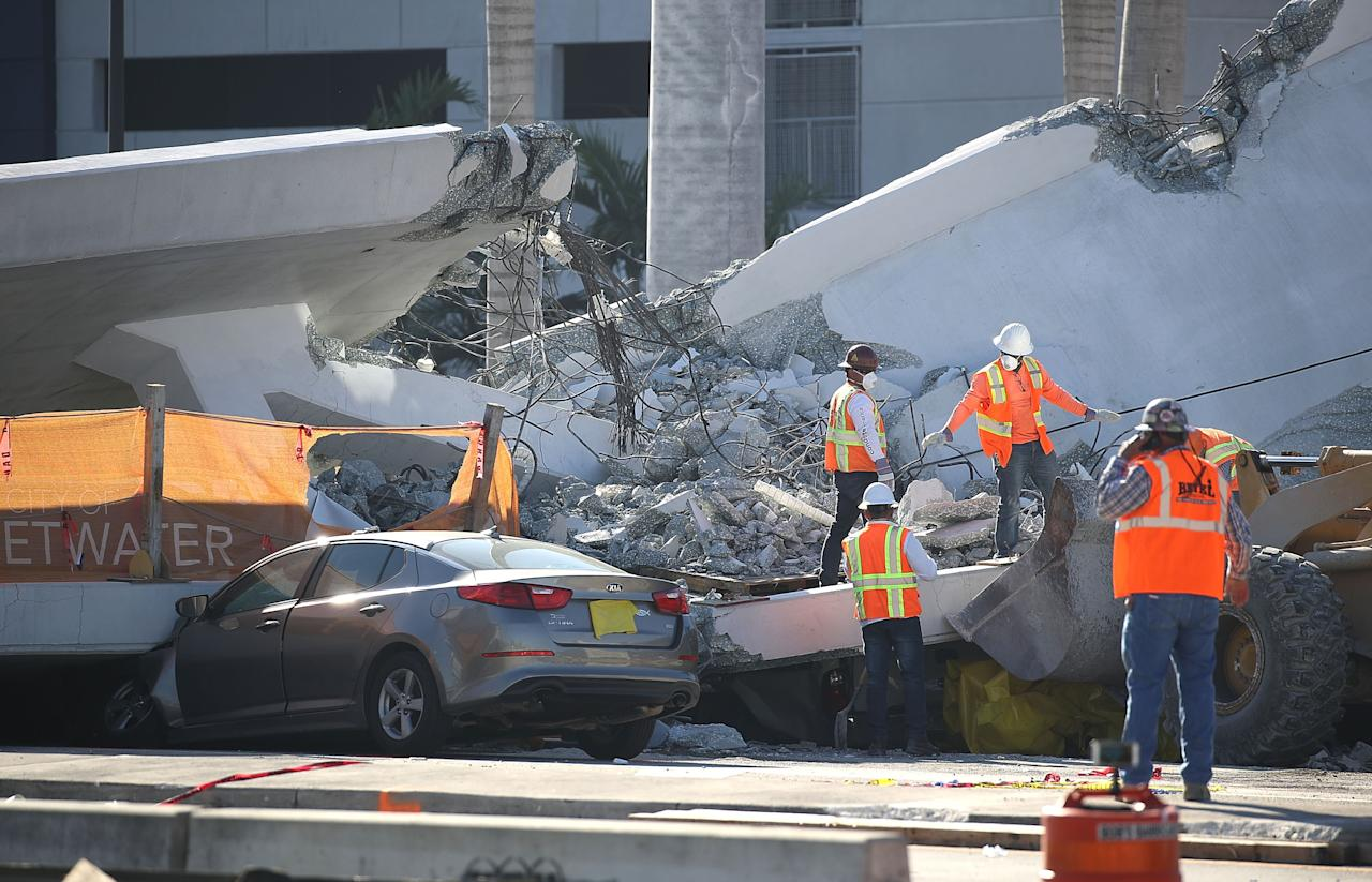 <p>Workers, law enforcement and members of the National Transportation Safety Board investigate the scene where a pedestrian bridge collapsed a few days after it was built over southwest 8th street allowing people to bypass the busy street to reach Florida International University on March 16, 2018 in Miami, Florida. (Photo: Joe Raedle/Getty Images) </p>