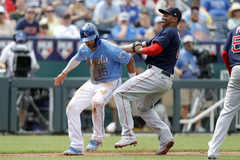 Kansas City Royals' Whit Merrifield, left, is tagged out by Boston Red Sox third baseman Rafael Devers, right, during a rundown between home plate and third base in the third inning of a baseball game at Kauffman Stadium in Kansas City, Mo., Saturday, June 19, 2021. (AP Photo/Colin E. Braley)
