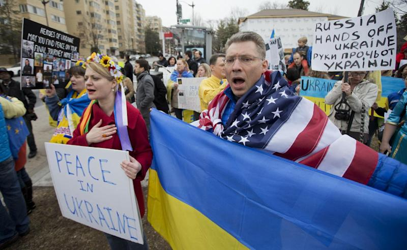 """Moscow-born Dmitry Savransky, right, who holds dual citizenship, American and Russian, joins his Ukrainian wife Natalya Seay, left, during a protest rally in front of the Russian embassy, in Washington, Sunday, March 2, 2014. Igniting a tense standoff, Russian forces surrounded a Ukrainian army base Sunday just as the country began mobilizing in response to the surprise Russian takeover of Crimea. Outrage over Russia's tactics mounted in world capitals, with U.S. Secretary of State John Kerry calling on President Vladimir Putin to pull back from """"an incredible act of aggression."""" (AP Photo/Manuel Balce Ceneta)"""
