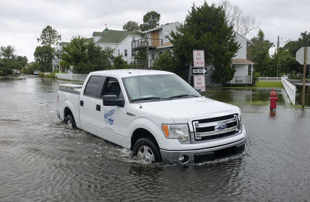 A city worker drives his truck through a flooded street after Hurricane Arthur passed through in Manteo, North Carolina July 4, 2014. REUTERS/Chris Keane