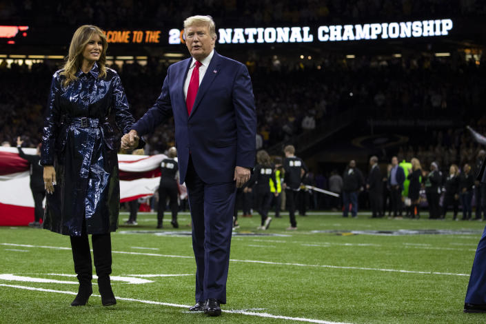 President Donald Trump and first lady Melania Trump walk off the field after the national anthem before the beginning of the College Football Playoff National Championship game between LSU and Clemson, Monday, Jan. 13, 2020, in New Orleans. (AP Photo/ Evan Vucci)