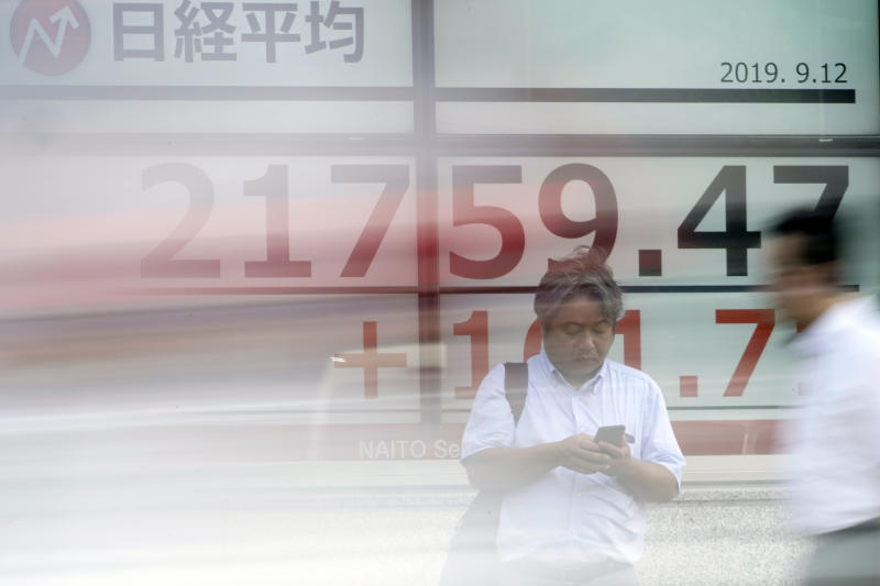 A man stands near an electronic stock board showing Japan's Nikkei 225 index at a securities firm in Tokyo Thursday, Sept. 12, 2019. Asian shares were mixed Thursday after China moved to ease trade tensions. (AP Photo/Eugene Hoshiko)
