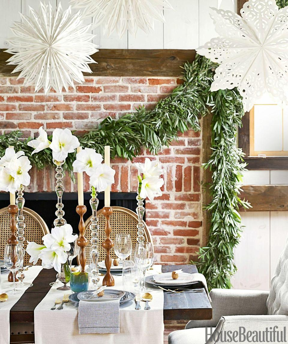 <p>Decorate using objects of different heights. Start by hanging oversized snowflakes, and building up the table with tall candlesticks. For the mantel, hang a garland made with olive branches. </p>