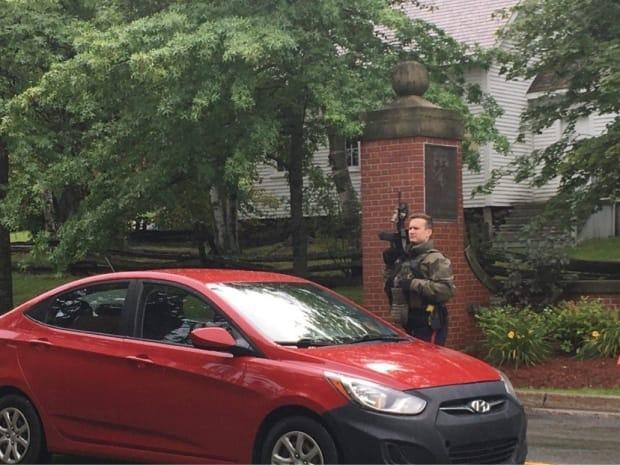 An armed police officer surveys the scene as vehicles evacuate the University of New Brunswick campus in Fredericton on Friday. (Brendan Ahern photo - image credit)