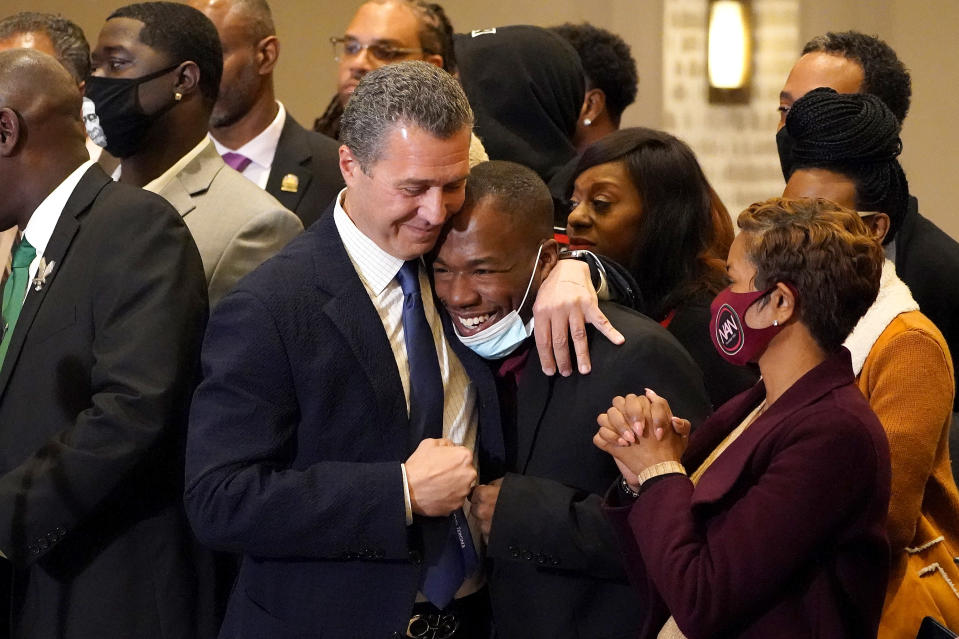 Attorney Tony Romanucci, center left, hugs Donald Williams, a key witness in the trial of former Minneapolis police Officer Derek Chauvin, during a news conference after the guilty verdict was read, Tuesday, April 20, 2021, in Minneapolis. (AP Photo/Julio Cortez)