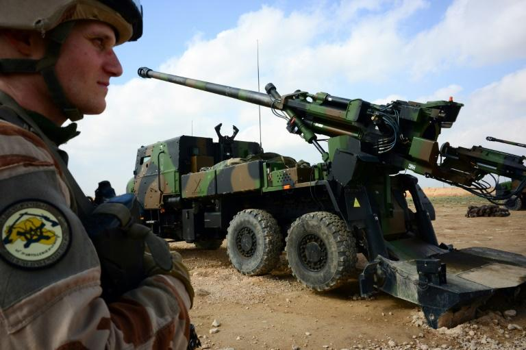 A French soldier stands guard in front of a howitzer-gun near Al-Qaim in Iraq on February 9, 2019