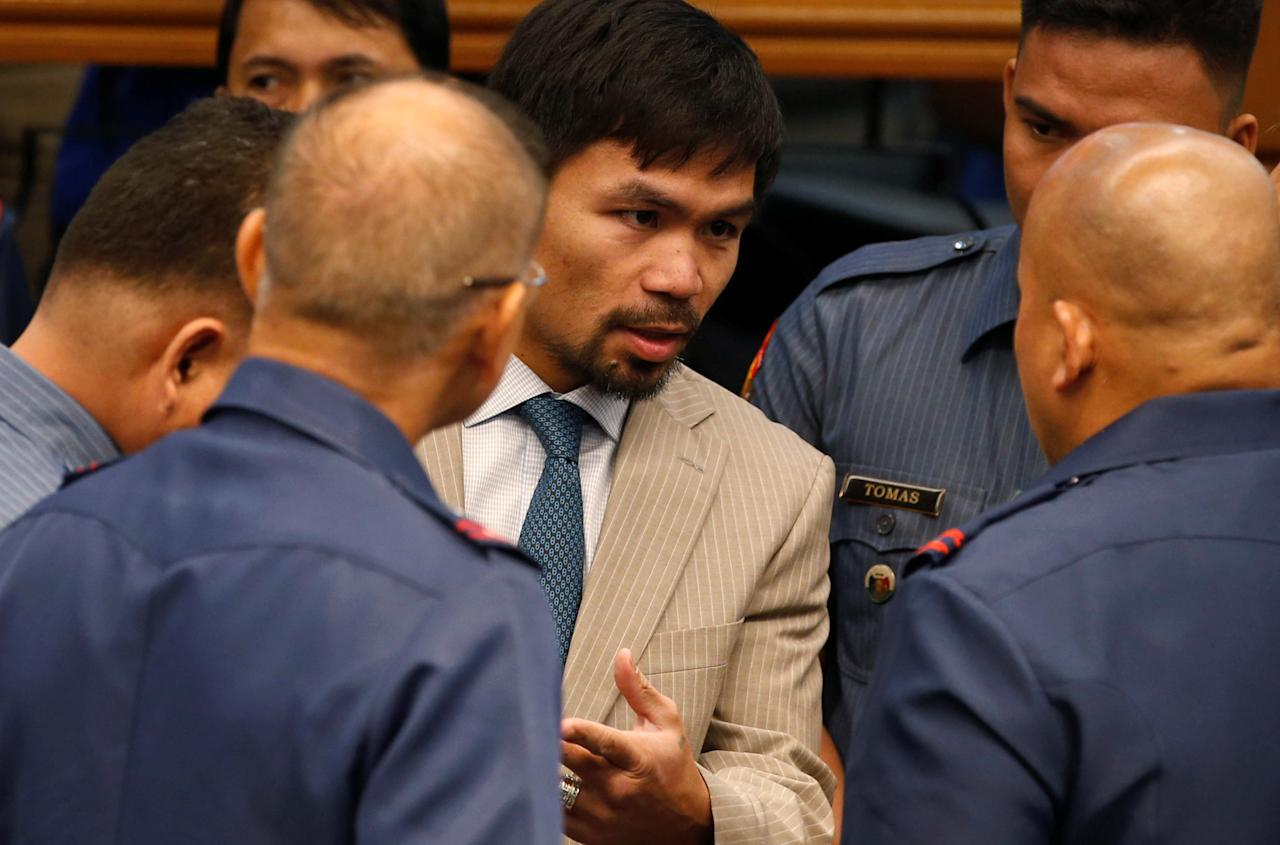 Filipino boxer and Senator Manny Pacquiao talks to Philippine National Police chief Director-General Ronald dela Rosa (back at the camera) and other police officers during a Senate hearing on crackdown on illegal drugs in Pasay, Metro Manila, Philippines August 23, 2016.  REUTERS/Erik De Castro