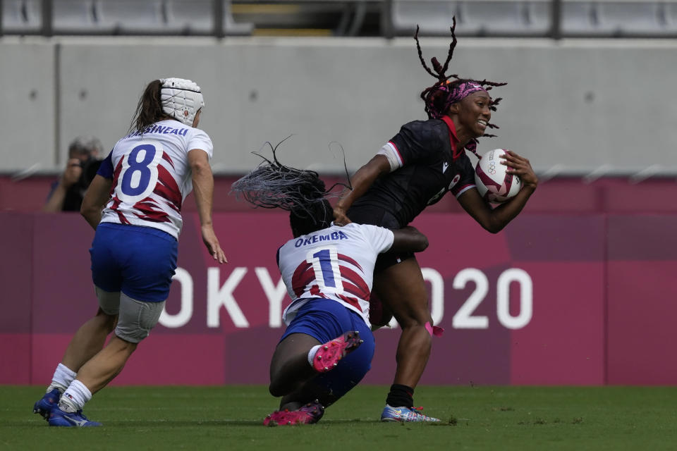 Canada's Charity Williams is tackled by France's Seraphine Okemba, in their women's rugby sevens match at the 2020 Summer Olympics, Friday, July 30, 2021 in Tokyo, Japan. (AP Photo/Shuji Kajiyama)