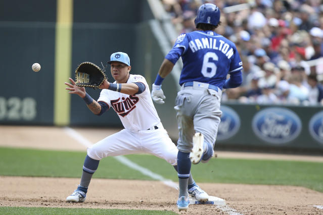 Minnesota Twins' Ehire Adrianza catches the ball at first to get out Kansas City Royals' Billy Hamilton after he bunted a ground ball during the fifth inning of a baseball game Sunday, June 16, 2019, in Minneapolis. Adrianza caught the ball from pitcher Martin Perez. (AP Photo/Stacy Bengs)
