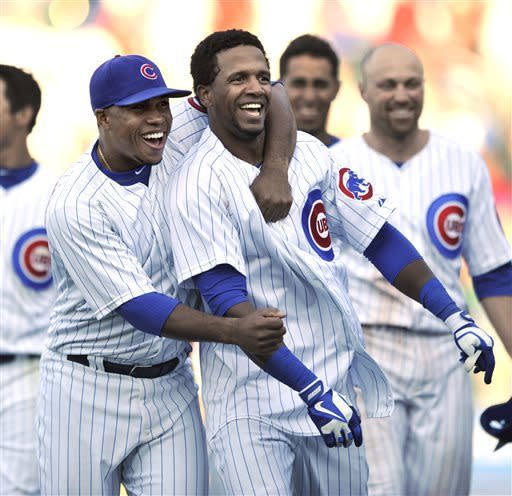 Chicago Cubs' Julio Borbon, front right, celebrates with teammate Luis Valbuena, left, after hitting a walkoff-single to defeat the Cincinnati Reds 6-5 in fourteen innings of an MLB baseball game in Chicago, Thursday, June 13, 2013. (AP Photo/Paul Beaty)