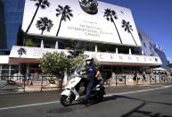 A police officer rides a scooter whilst passing the Palais des during preparations for the 74th international film festival, Cannes, southern France, July 5, 2021. The Cannes film festival runs from July 6 - July 17, 2021. (AP Photo/ Brynn Anderson)