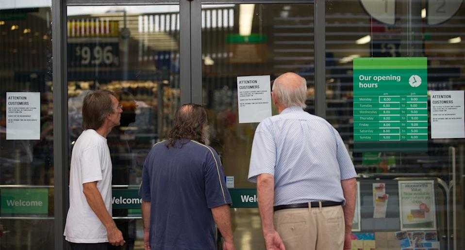 Photo shows customers standing outside a closed Woolworths store.