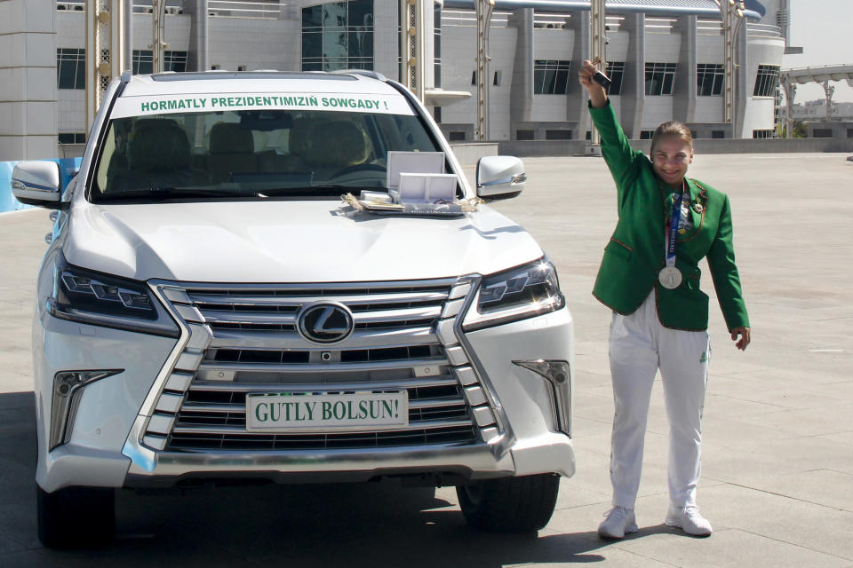 ADDS CLASS OF MEDAL Polina Guryeva, Olympic silver medalist in the women's 59kg weightlifting event at the 2020 Summer Olympics, shows the key of her new car, a gift from the Turkmenistan President at a lavish ceremony in Ashgabat, Turkmenistan, Saturday, Aug. 21, 2021. Turkmenistan has lauded its first Olympic medal winner at a lavish ceremony where she was showered with gifts. Guryeva, 21, lifted a total 217 kilograms in the 59-kilogram category, edging Mikiko Andoh of Japan for second place at the Tokyo Games. (AP Photo/Alexander Vershinin)