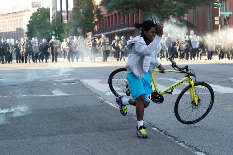 A protestor grabs his bike as the police use tear gas and rubber bullets to disperse the crowd gathered near the White House on June 1, 2020 (AFP Photo/ROBERTO SCHMIDT)