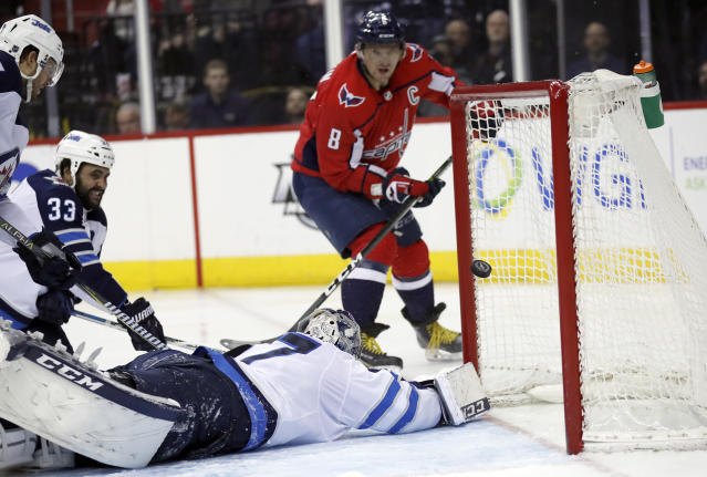 Washington Capitals left wing Alex Ovechkin (8) watches his shot get past Winnipeg Jets goaltender Connor Hellebuyck (37) for a goal in the second period of an NHL hockey game, Monday, March 12, 2018, in Washington. It was Ovechkin's 600th career goal. (AP Photo/Alex Brandon)