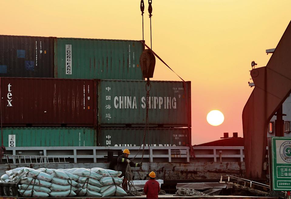 Workers loading ships at a port in Nantong, in China's eastern Jiangsu province, on March 9, 2018.