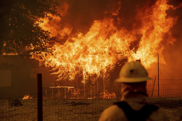 <p>A firefighter monitors a burning outbuilding to ensure flames don't spread as the River Fire burns in Lakeport, Calif., on Monday, July 30, 2018. A pair of wildfires that prompted evacuation orders for nearly 20,000 people barreled Monday toward small lake towns in Northern California, and authorities faced questions about how quickly they warned residents about the wildfires. (Photo: Noah Berger/AP) </p>