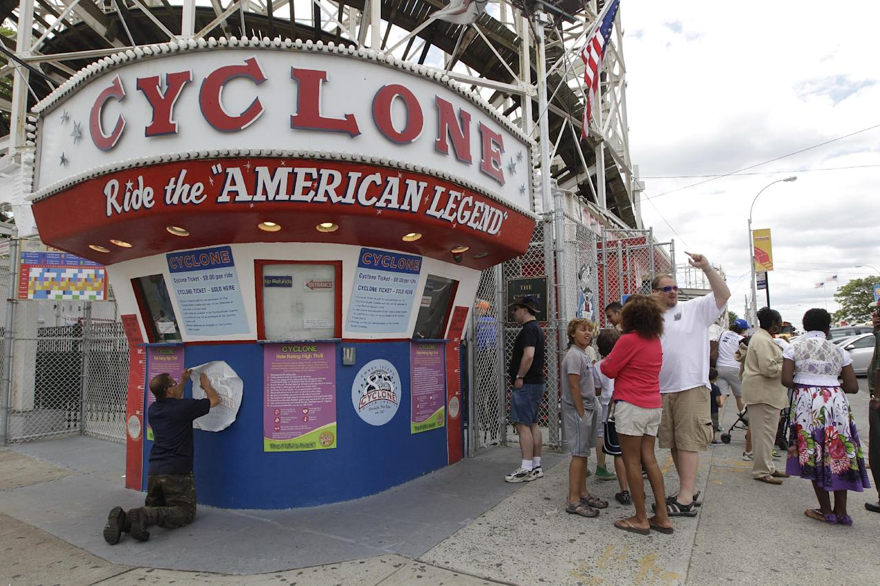 In a Tuesday, June 26, 2012 photo taken on Coney Island in New York, a maintenance worker applies a decal commemorating the Cyclone's 85th anniversary while people wait in line to buy tickets. The New York City landmark and international amusement icon will be feted Saturday, June 30 with a birthday party in its honor. (AP Photo/Mary Altaffer)