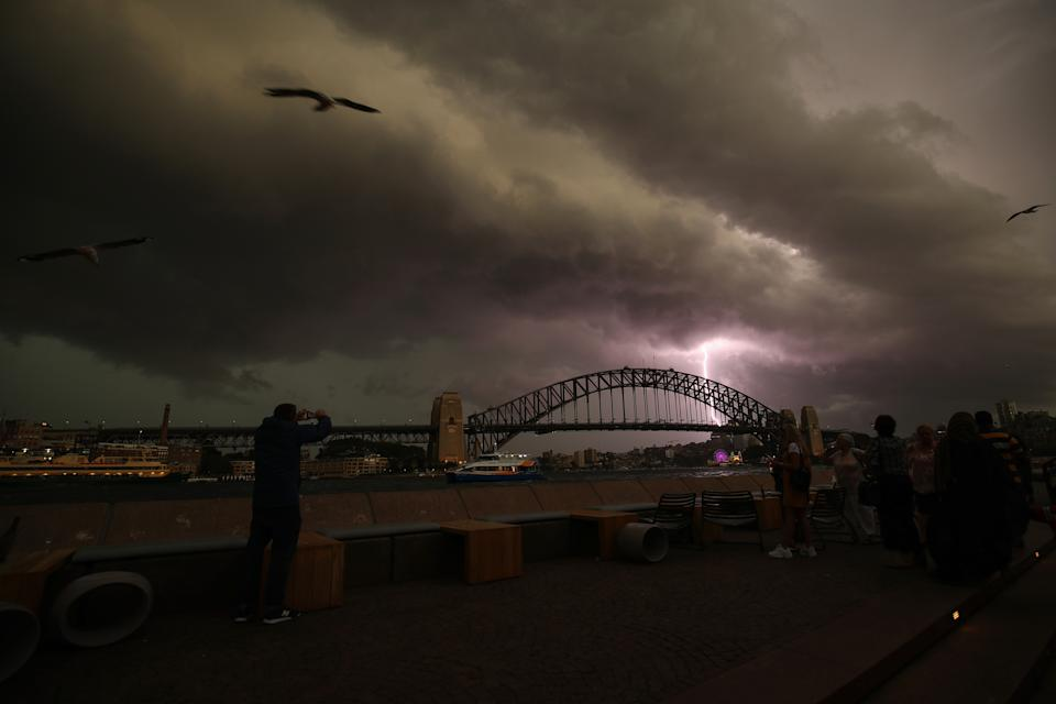 A lightning bolt strikes as a storm cell is seen above the Sydney Harbour Bridge in Sydney, Saturday, October 20, 2018.