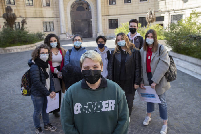 Matteo Coccimiglio poses for a photos with his schoolmates in front of the Ripetta art school in Rome, Wednesday, March 24, 2021. Matteo is an 18-year-old student who identifies as a man and is in the process of changing his legal gender from female to male. The Ripetta school of art in Rome - where he studies - recently joined a handful of high schools in Italy that give transgender students the right to be known by a name other than the one they were given at birth. The initiative is meant to create an environment where transgender students feel secure and reflects a growing awareness in Italy of gender dysphoria among teenagers and children. (AP Photo/Alessandra Tarantino)