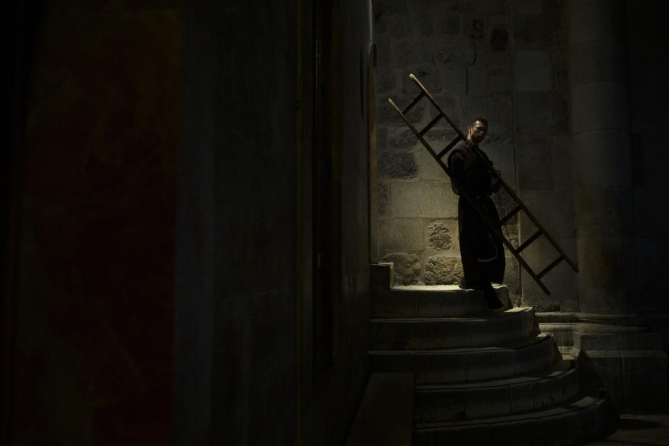 A priest carries a ladder used as a barrier to a chapel during mass at the Church of the Holy Sepulchre, where Jesus Christ is believed to be buried, in the Old City of Jerusalem, Thursday, Oct. 22, 2020. The site has seen very few visitors since measures to curb the spread of the coronavirus began. (AP Photo/Maya Alleruzzo)