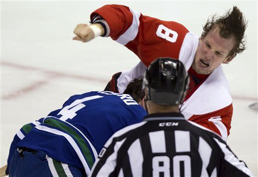 Detroit Red Wings' Justin Abdelkader, right, and Vancouver Canucks' Keith Ballard fight as linesman Thor Nelson watches during the second period of an NHL hockey game in Vancouver, British Columbia, on Saturday, April 20, 2013. (AP Photo/The Canadian Press, Darryl Dyck)