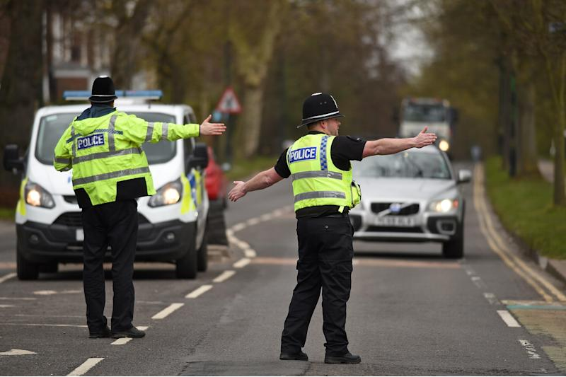 "Police officers from North Yorkshire Police stop motorists in cars to check that their travel is ""essential"", in line with the British Government's Covid-19 advice to ""Stay at Home"", in York, northern England on March 30, 2020, as life in Britain continues during the nationwide lockdown to combat the novel coronavirus pandemic. - Life in locked-down Britain may not return to normal for six months or longer as it battles the coronavirus outbreak, a top health official warned on Sunday, as the death toll reached passed 1,200. (Photo by Oli SCARFF / AFP) (Photo by OLI SCARFF/AFP via Getty Images)"