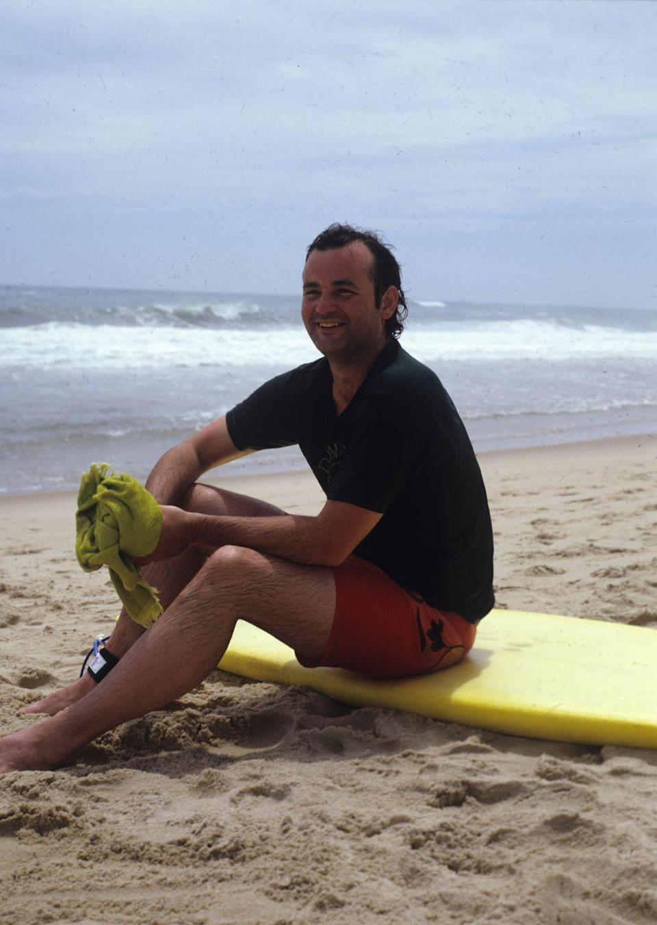 <p>Portrait of Bill Murray, in a t-shirt and swimming trunks, as he sits on a yellow surfboard on the beach during a photoshoot for Rolling Stone magazine, 1981.</p>