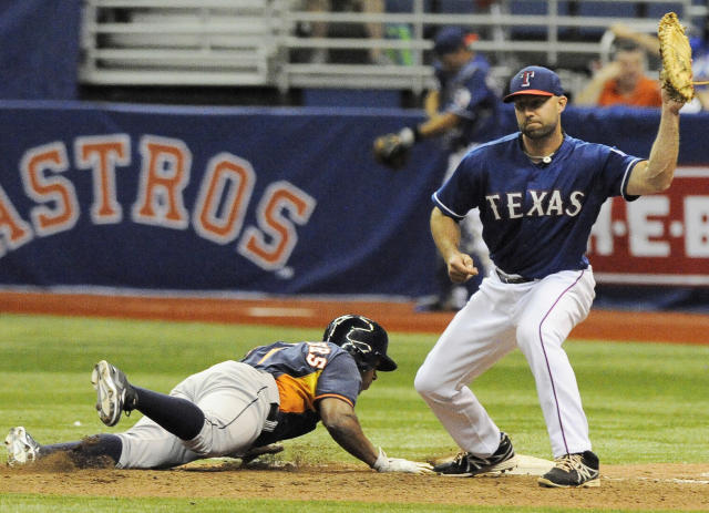 Houston Astros' Adron Chambers, left, dives safely back to first base against Texas Rangers' Kevin Kouzmanoff during a spring exhibition baseball game on Friday, March 28, 2014, in San Antonio. Houston won 6-5. (AP Photo/Darren Abate)
