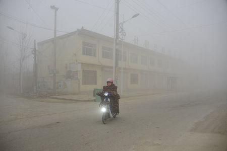 FILE PHOTO: A cyclist rides along a street in heavy smog during a polluted day in Liaocheng