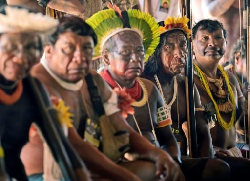Indigenous tribesmen listen to chief Raoni Metuktire (out of frame) during a press conference in Piaracu village, near Sao Jose do Xingu, Mato Grosso state, Brazil