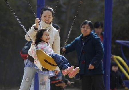 A mother pushes her daughter on a swing in Beijing, April 3, 2013. REUTERS/Jason Lee/Files