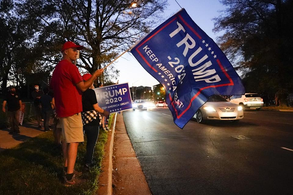 A man holds a Trump 2020 Keep America Great flag on the side of a road as cars drive by