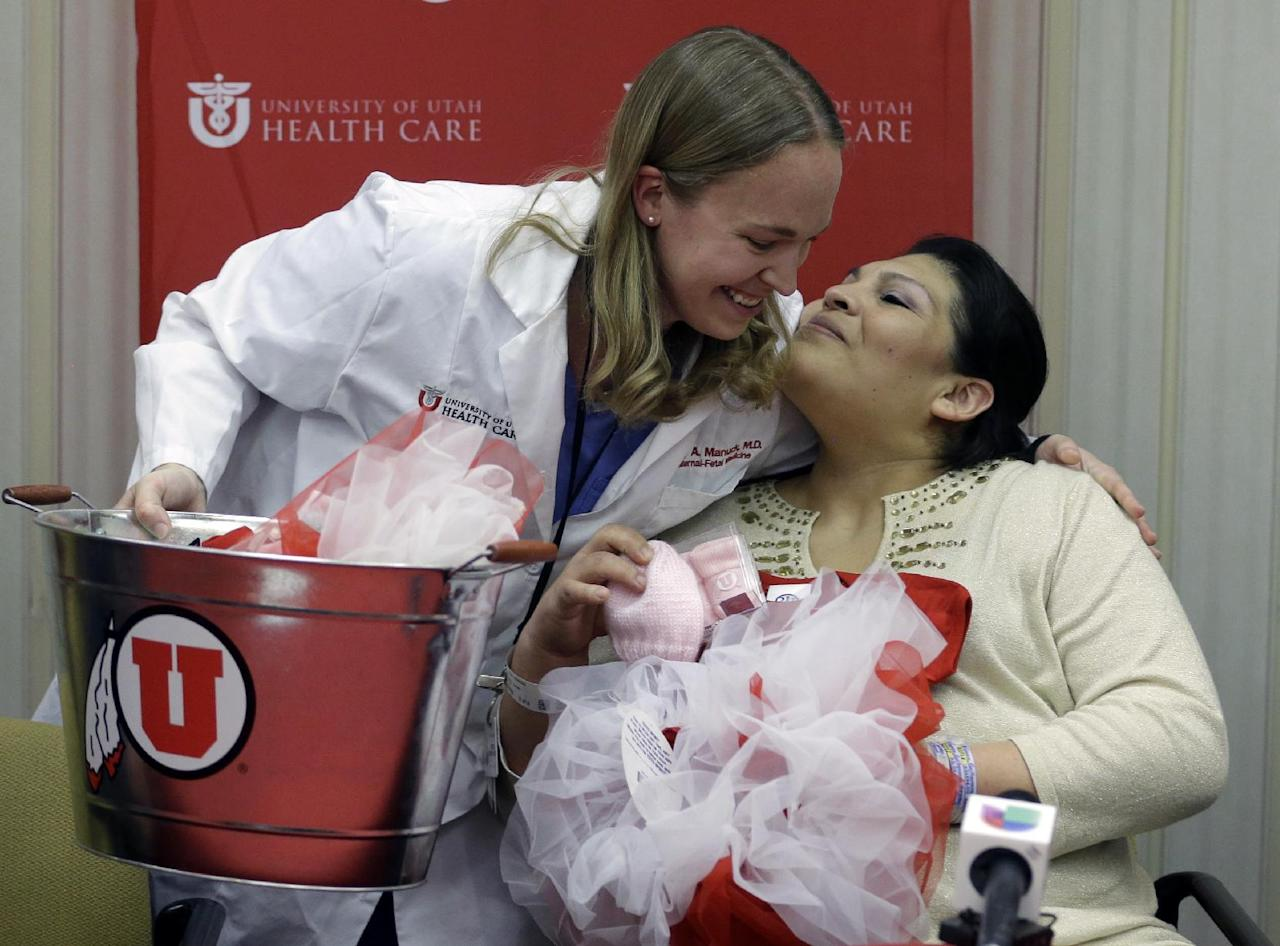 Dr. Tracy Manuck, left, receives a hug from Guillermina Garcia after getting a baby present following a news conference Tuesday, May 28, 2013, at the University of Utah hospital, in Salt Lake City. A team about 40 medical personnel led by eight doctors helped ensure a Utah couple's newborn quintuplets were born healthy. Guillermina and Fernando Garcia welcomed their five babies — three girls and two boys — over the weekend at the University of Utah hospital in Salt Lake City. (AP Photo/Rick Bowmer)