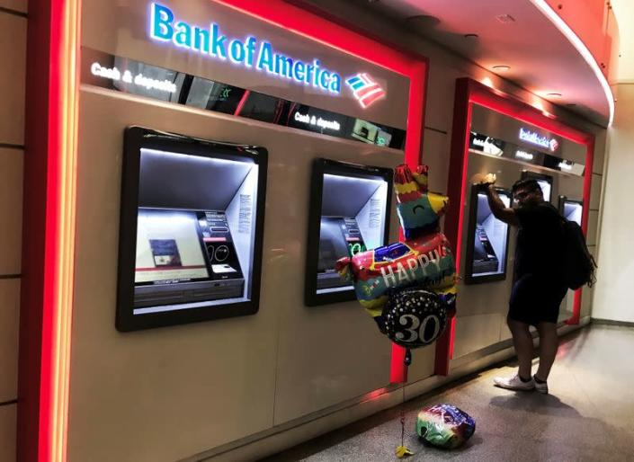 FILE PHOTO: A man uses an ATM machine next an inflatable plastic balloon inside a Bank of America branch in Times Square in New York