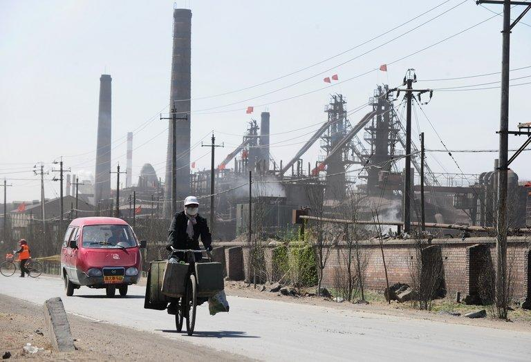 A cyclist rides past dozens of factories processing rare earths on the outskirts of Baotou city on April 21, 2011