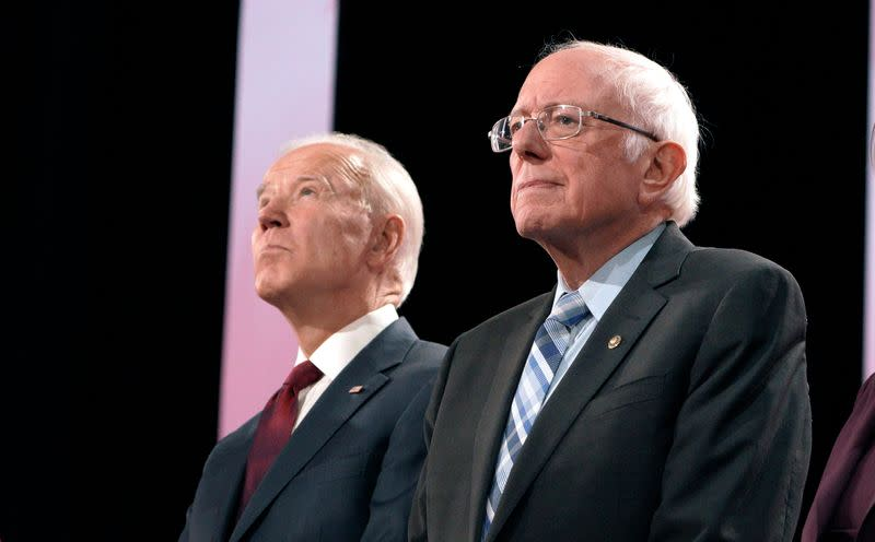 Former Vice President Joe Biden and Senator Bernie Sanders stand together on stage before the start of the sixth 2020 U.S. Democratic presidential candidates campaign debate at Loyola Marymount University in Los Angeles