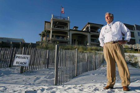 Coastal engineer Terry Anderson stands near the dunes that he created behind former Arkansas Governor Mike Huckabee's house (top C) on the Gulf Coast in Santa Rosa Beach, Florida, June 29, 2014. Picture taken June 29, 2014. REUTERS/Phil Sears