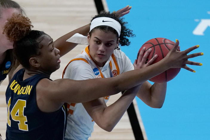 Michigan guard Akienreh Johnson (14) pressures Tennessee guard Rae Burrell during the first half of a college basketball game in the second round of the women's NCAA tournament at the Alamodome in San Antonio, Tuesday, March 23, 2021. (AP Photo/Charlie Riedel)