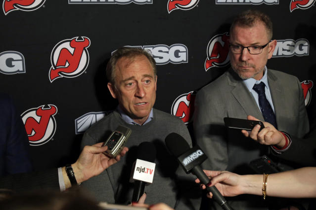 New Jersey Devils owner Josh Harris, left, announces interim general manager Tom Fitzgerald, right, to replace Ray Shero prior to an NHL hockey game Sunday, Jan. 12, 2020, in Newark, N.J. (AP Photo/Adam Hunger)