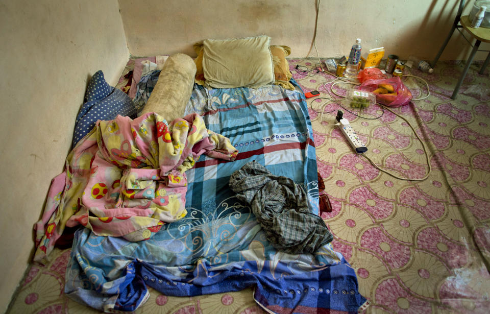 """Pillows and blankets are seen in the sleeping area of Bangladeshi palm oil worker, Karim, at a house he shares with others in peninsular Malaysia, Wednesday, March 6, 2019. """"I have been cheated five times in six years,"""" said Karim, a migrant worker who arrived in Malaysia legally after being promised a position in an electronics company, only to end up working for a subcontractor on several plantations owned by the biggest companies. He says once when he asked for his unpaid wages, his boss """"threatened to run me over with his car."""" (AP Photo/Gemunu Amarasinghe)"""