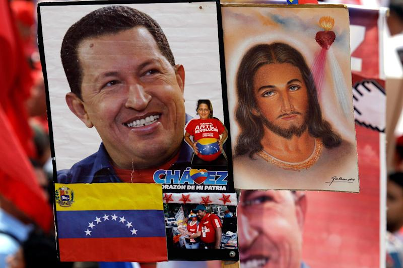 A photograph of Venezuela's President Hugo Chavez, left, flanks one of Jesus Christ, held by a Chavez supporter at a rally in Caracas, Venezuela, Wednesday, Jan. 23, 2013. The cult of personality that Chavez long nurtured has been flourishing like never before as he confronts an increasingly difficult struggle against the mysterious cancer that afflicts him. The connections between Chavez and Jesus are surfacing more often, having begun with Chavez himself praying to God on television, and repeatedly kissing a crucifix. (AP Photo/Fernando Llano)