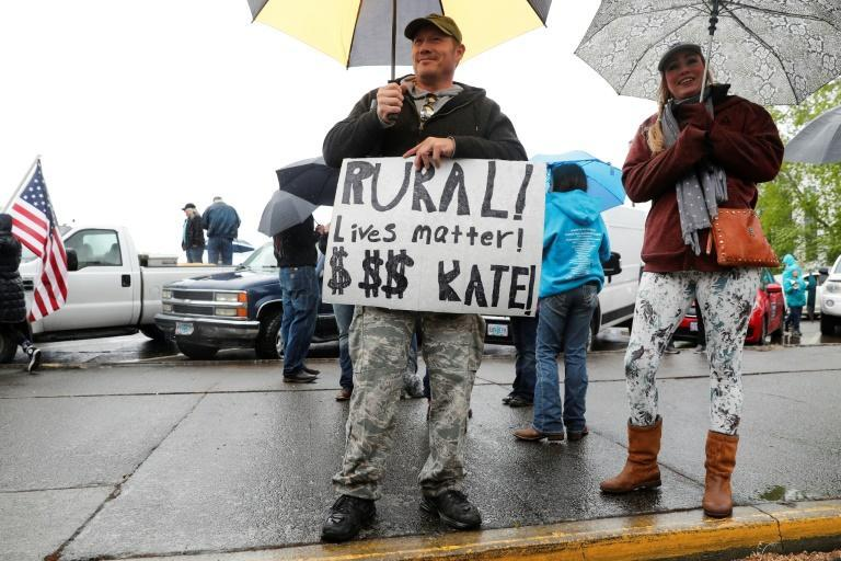 """Justin Ford, of Grants Pass, holds a sign that says """"Rural lives matter, Kate!"""" at the ReOpen Oregon Rally against coronavirus restricitons on May 2, 2020 in Salem, Oregon"""