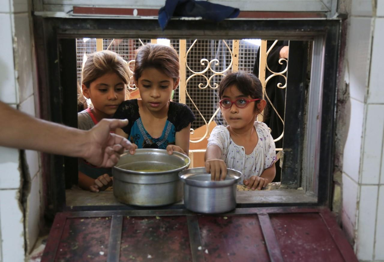 <p>Girls receive free food for their families distributed for iftar, the evening meal breaking the Ramadan fast, at the Abdul Khader al-Kilani mosque in Baghdad, June 8, 2016. (AP/Karim Kadim) </p>