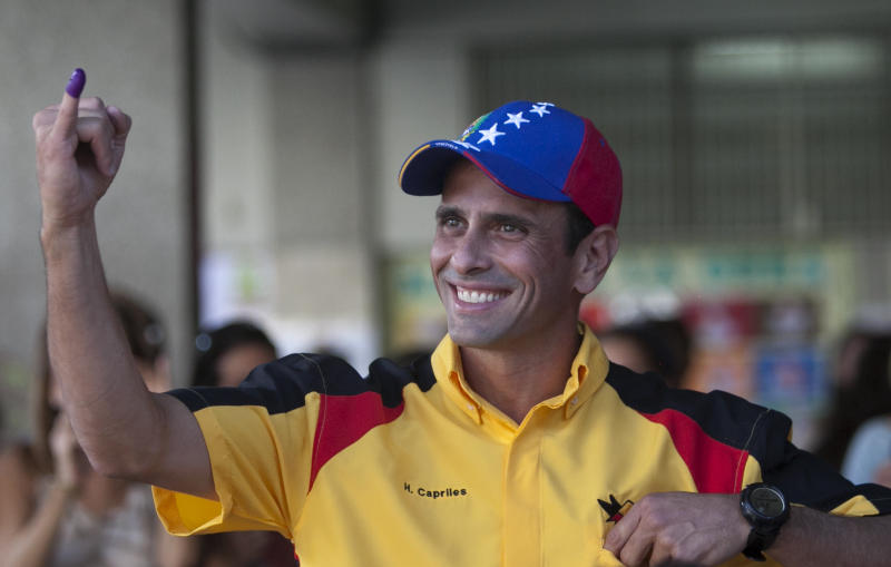 Henrique Capriles, governor of the state of Miranda and former presidential candidate shows his finger marked with ink after casting his vote during municipal elections in Caracas, Venezuela, Sunday, Dec. 8, 2013. Venezuelans head to the polls to elect mayors and city councilors at a moment when the country's economic troubles have deepened, with inflation touching a two-decade high of 54 percent, and shortages of everything from toilet paper to milk spreading while the black market value of the currency plunges.(AP Photo/Alejandro Cegarra)