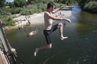 Patrons of the Bitterroot River jump into the cool water as temperatures crested 100 degrees in Missoula, Montana, on Wednesday, June 30, 2021. (AP Photo/Tommy Martino)